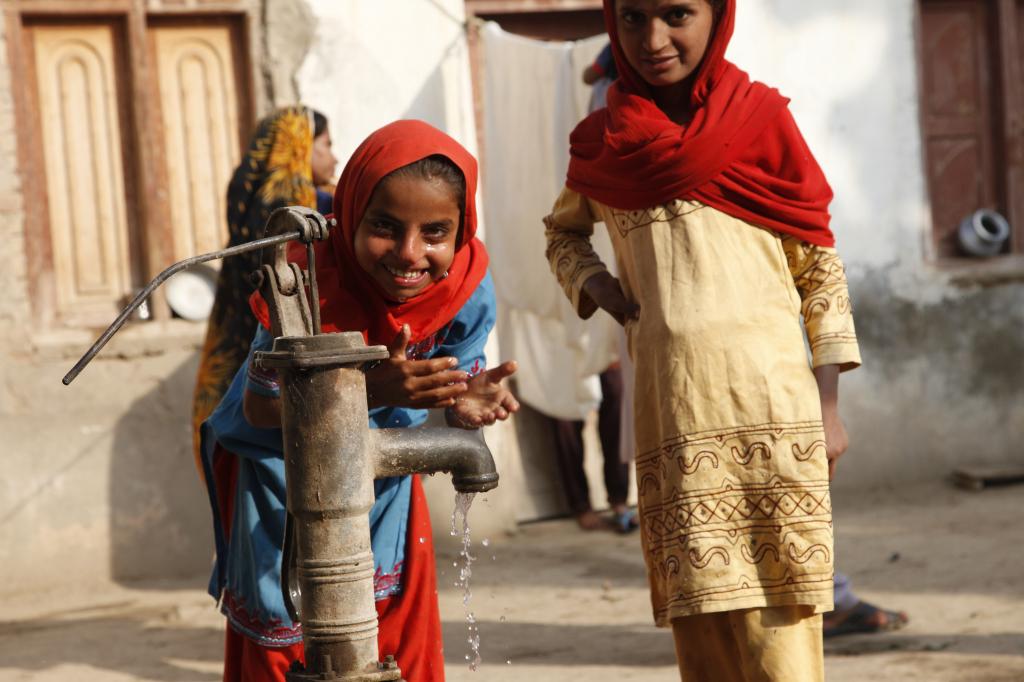 Zwei pakistanische Mädchen an einem Handbrunnen