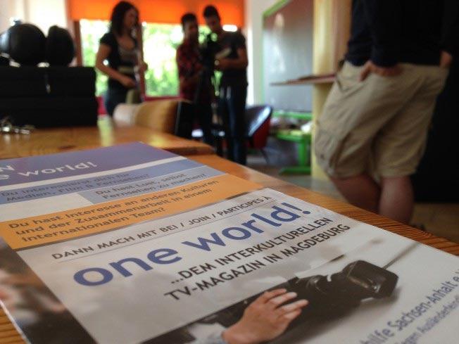 Poster One World auf Tisch, Menschen im Hintergrund