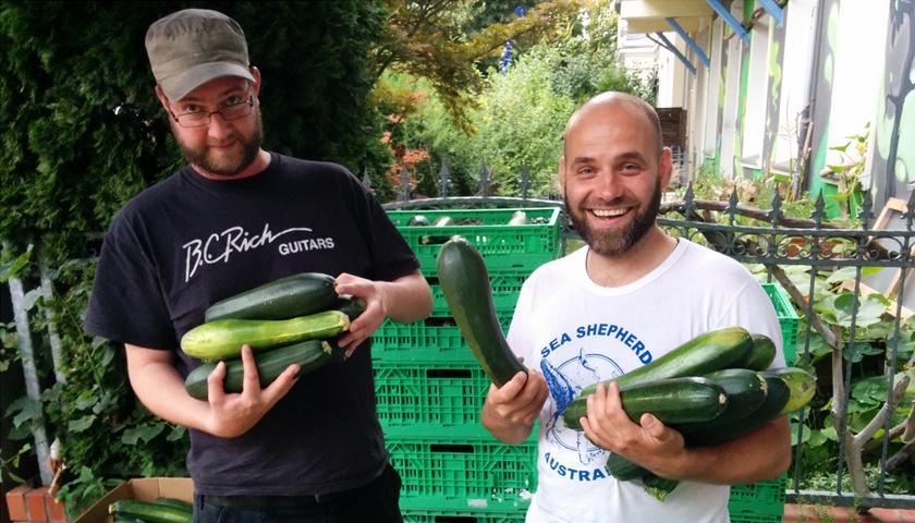 Zwei Männer mit mehreren Zucchinis im Arm