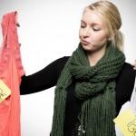 Junge Frau blickt prüfend auf zwei Kleidungsstücke