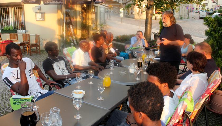 Verschiedene Menschen an zusammengestellten Cafe-Tischen